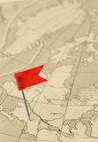 Red flag a pin on old map Stock Photography