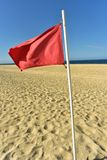 Red flag on flag pole blowing in wind. Red flag on flag pole blowing in breeze on seashore beach with blue sky background stock images