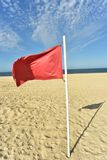 Red flag on flag pole blowing in wind. Red flag on flag pole blowing in breeze on seashore beach with blue sky background royalty free stock images