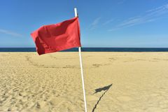 Red flag on flag pole blowing in wind. Red flag on flag pole blowing in breeze on seashore beach with blue sky background stock photo