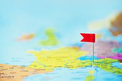 Red flag, pushpin, thumbtack pinned on map of europe. Copy space, travel concept.  Stock Images