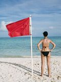 Red flag on the sea Stock Photos
