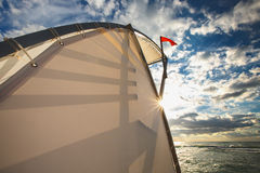 Red flag and sea, ocean beach sunrise with deep blue sky and sun rays Royalty Free Stock Image