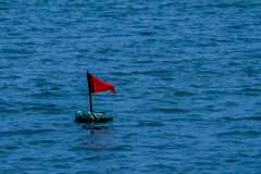 Red flag in the sea stock images