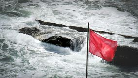 Red flag sea rocks rough storm gale wind alert background.  Royalty Free Stock Photography