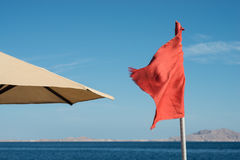 Red flag at sea. Swimming is prohibited Stock Images