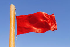Red flag to develop on the background of blue sky Stock Photography
