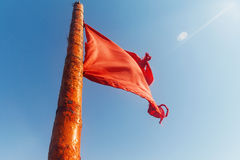 Red flag to develop on the background of blue sky Stock Image