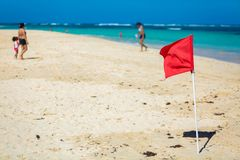 Red Flag warning sign at the beack no swimming. Waves royalty free stock photo