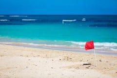 Red Flag warning sign at the beack no swimming. Waves royalty free stock image