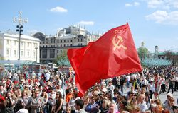 Red flag waves above people's heads. Stock Photos