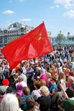Red flag waves above people's heads. Royalty Free Stock Photo