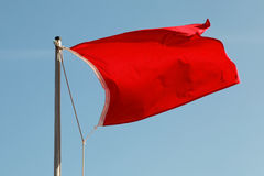 Red flag waving above blue sky Stock Photography