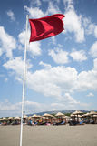 Red flag, white pole, blue cloudy sky and sandy be. Sea shore, summer, windy weather sign flag Stock Images