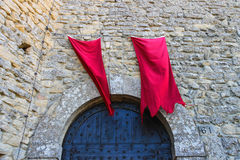 Red flags over the gates fortresses in San Marino. Royalty Free Stock Photos