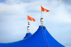 Red flags on top of circus tent. Red flags on top of circus blue tent clouse up and sky Royalty Free Stock Images