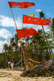 Red flags on tropical white sand beach with palm trees Philippines. Boracay island Stock Photography