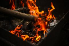Red flame from a cut of a tree, dark gray coals inside a metal brazier. Firewood burning in a brazier on a bright yellow flame stock photography