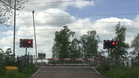 Red flashing lights at a level crossing. Red flashing lights warning that the barrier is down and a train is coming stock video