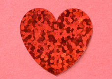 Red flat shiny foil heart on pink tectured paper background close up Royalty Free Stock Image