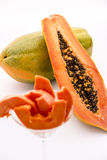 Red-fleshed Papaya. A longitudinal section across the globose body of a papaya fruit does reveal its red-fleshed pulp and countless black seeds in its central Royalty Free Stock Images