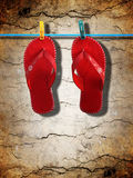 Red flip-flops. Against dirty cracked wall background Stock Image