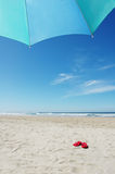 Red Flip Flops. A pair of red flip flops lying beside a beach umbrella royalty free stock images