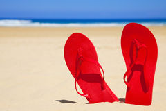 Red Flip-flops in the beach. Standing red sandals in a empty sea beach Royalty Free Stock Image