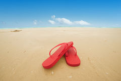 Red flip flops on the beach. Sand.Concept of summer vacations Royalty Free Stock Photo