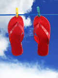 Red flip-flops on clothes line. Under summer sky Stock Photos