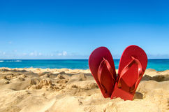 Red flip flops in heart shape on the sandy beach Royalty Free Stock Photo