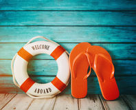 Red flip flops sandals on wood. Red flip flops sandals and life preserver on wood Royalty Free Stock Photos