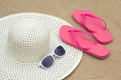 Red flip flops, sunglasses and hat on sandy beach Royalty Free Stock Images