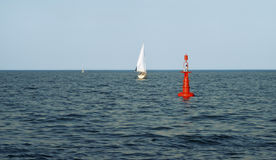 Red floating buoy in the Baltic Sea, powered by solar energy Royalty Free Stock Photography