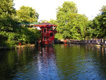 A red floating Chinese restaurant Feng Shang Princess hidden by the side of the Regent`s Canal in Camden stock photo