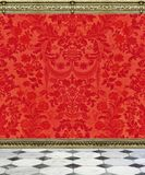 Red Damask Wall and Marble Floor. Red flocked damask wallpaper with gray and white marble floor and ornate moldings royalty free stock photography