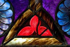 Red Flowe Petals Depicted in Stained Glass Window. Three red flower petals with blue flower petals depicted in a church stained glass window. Colors included are Royalty Free Stock Photography