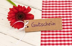 Red flower with gift tag and german word, Gutschein, means voucher or coupon. Gift card with red gerbera daisy flower and german word, Gutschein, means voucher Royalty Free Stock Image