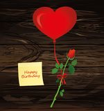 Red flower hanging on a ribbon with a bow on a hot air balloon i. N the shape of a heart. Greeting card or invitation for a holiday.Yellow sheet of paper for Stock Images