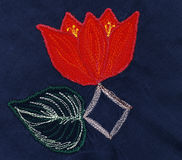 Red flower with leaf. Applique on blue fabric. Red flower with leaf. Applique on gark blue fabric Royalty Free Stock Photo