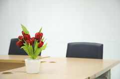 Red flower on Meeting room table. Two black chairs in a meeting room with Red flower on Meeting room tablet Stock Photography