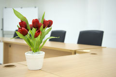 Red flower on Meeting room table. Two black chairs in a meeting room with Red flower on Meeting room tablet and white board in the background Stock Photos