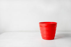 Red flower pot. On white wooden background royalty free stock images