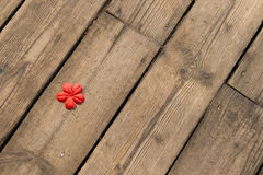 Red flower on the wooden floor. Red fabric artificial flower on the background of the wooden floor royalty free stock image