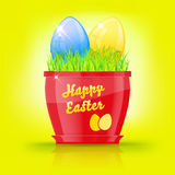 Red flowerpot with green grass and easter eggs Stock Image