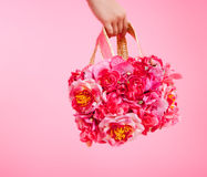 Red flowers bag in woman hand on pink background Stock Image