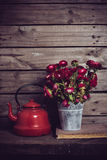 Red flowers and enamel kettle Royalty Free Stock Photo