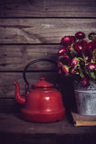 Red flowers and enamel kettle. Rustic red flowers in a can vase and an old enamel kettle on an old vintage wooden board background. Country kitchen decor stock images