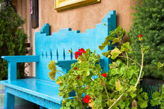 Red Flowers in Front of an Antique Bench Stock Image