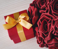 Red flowers and gift box with yellow ribbon Royalty Free Stock Image